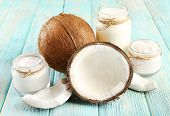 picture of flesh  - Fresh coconut oil in glassware on color wooden table background - JPG