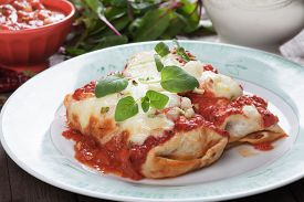 stock photo of enchiladas  - Mexican enchilada dish with tortillas in chili sauce - JPG
