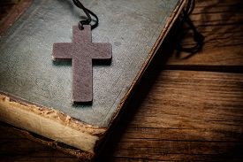 stock photo of christianity  - Closeup of wooden Christian cross on bible - JPG