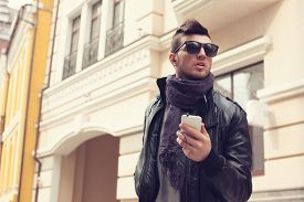 stock photo of snickers  - Guy in sunglasses and earphones on the street - JPG