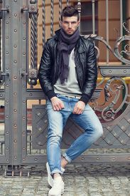 stock photo of snickers  - Fashionable man posing in old city - JPG