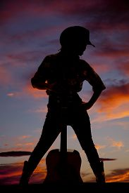 stock photo of cowgirls  - a silhouette of a cowgirl with her guitar between her legs - JPG