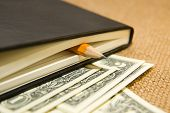 foto of memento  - notebook with a blank sheet pencil and money on the old tissue - JPG