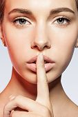image of taboo  - Portrait of beautiful woman with a finger to his lips - JPG