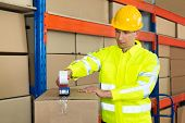 stock photo of dispenser  - Young Worker Packing Cardboard Box With Tape Gun Dispenser In Warehouse - JPG