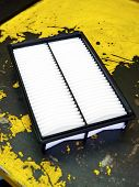 image of motor vehicles  - Clean motor vehicle air filter waiting to be installed during a service of the car lying on a yellow workbench in the repair workshop or garage - JPG
