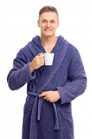 picture of mug shot  - Vertical shot of a young man in a blue bathrobe holding a coffee mug and looking at the camera isolated on white background - JPG