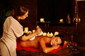 Masseur do massage of woman in spa salon. Girl on candles background in massage spa salon. Luxary in poster
