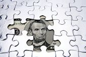 U.S. five dollar banknote and jigsaw puzzle