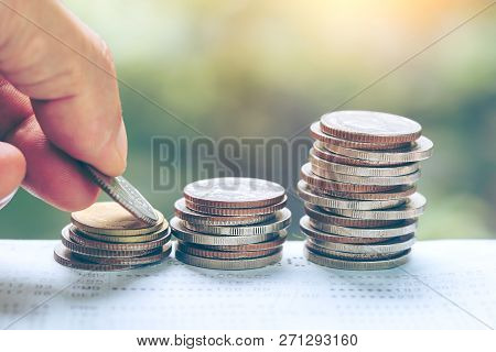 poster of Business And Money Saving Concept - Close Up Of Man Hand Putting Euro Coins Into Columns, Coins Stac