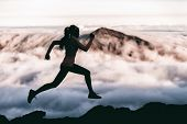 Trail runner athlete silhouette running in mountain summit background clouds and peaks background. W poster