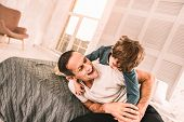 Energetic Kid Play-wrestling With His Dad On The Bed. poster