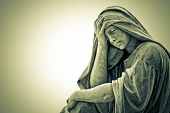 Vintage image of a marble statue representing a suffering religious woman