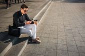 Well-dressed Young Man Sit On Steps Outside And Look At Phone. He Hold Cup Of Coffee. Leather Bag Is poster