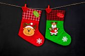 Decorative Christmas Socks. Empty Socks For Gift Hanging Off A Thread On Black Background Top View poster