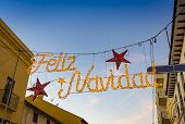 Merry Christmas (feliz Navidad) Inscription And Christmas Decorations On The Street In Center Of Ron poster