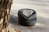 Used Car Tires Stacked On Top Of Each Other On The Road At The Curb. Obstacle For Spontaneous Parkin poster