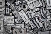background of random vintage letterpress metal type printing blocks, black and white image poster