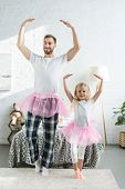 Happy Father And Adorable Little Daughter In Pink Tutu Skirts Dancing And Smiling At Camera poster