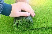 Hand Of A Worker With A Artificial Lawn Grass. Artificial Turf Laying Background. poster