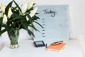 Orange Notebook, Glassses, Blue E-book With Plans For Today Desk And A Bouquet Of Beautiful White Li poster