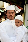 JAKARTA, INDONESIA - SEPTEMBER 20: A man and his son pose for a picture on their way to prayer at th