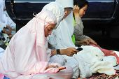 JAKARTA, INDONESIA - SEPTEMBER 20: Muslim girls send text messages on mobile phones between prayers outside a mosque on Hari Raya, the end of a month of fasting called Ramadan September 20, 2009 in Jakarta.