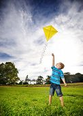 Young boy flies his kite in an open field. a pictorial analogy for aspirations and aiming high