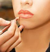 Applying lips contour closeup