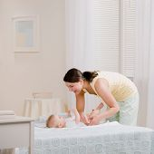 Loving mother changing baby?s diaper on bed