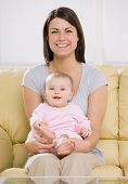Loving mother holding baby on sofa at home