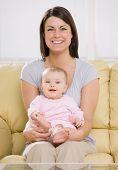 Amorosa mãe bebê de exploração no sofá em casa