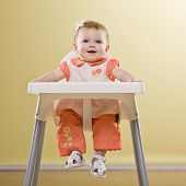 Happy baby girl sitting in highchair waiting to be fed