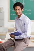 Confident teacher holding school book posing in classroom
