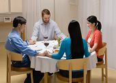 Religious couples saying prayer before elegant dinner party