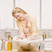 Devoted mother give baby girl a bath