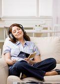 Mujer relajada en auriculares disfrutar escuchando música cd en la sala de estar