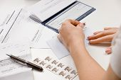 Woman writing checks from checkbook to pay monthly bills and stamping return envelope