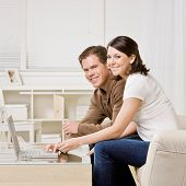 Happy couple typing on laptop in livingroom
