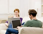 Couple relaxing on sofa in livingroom typing on laptops