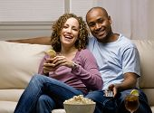 Relaxed couple with popcorn and remote control, drinking and watching television
