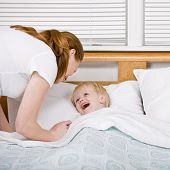 Devoted mother putting talkative son to bed at bedtime