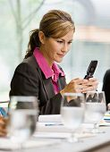 Businesswoman text messaging on cell phone in conference room