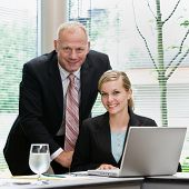 Businessman and female co-worker?s posing with laptop in conference room