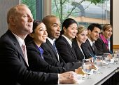 Multi-ethnic co-workers sitting in a row at conference table