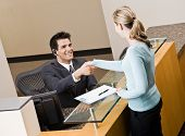 Friendly receptionist greeting woman at front desk and shaking hands
