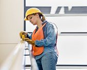 Female construction worker carefully taking measurement with measuring tape