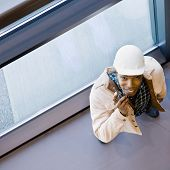 High angle view of African construction worker in hard-hat talking on cell phone
