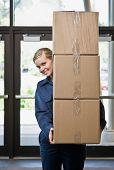 Delivery woman in uniform carefully carrying stack of cardboard boxes