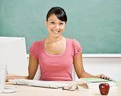 Maestro feliz sentado en el escritorio con ordenador en el aula de la escuela